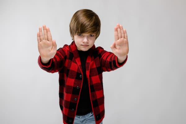 Portrait of serious little boy wearing checkered jacket and holding palms in front of him stop sign gesture isolated on grey background with copyspace.